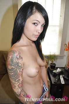 Gorgeous mixed race babe goes topless and shows tattoos